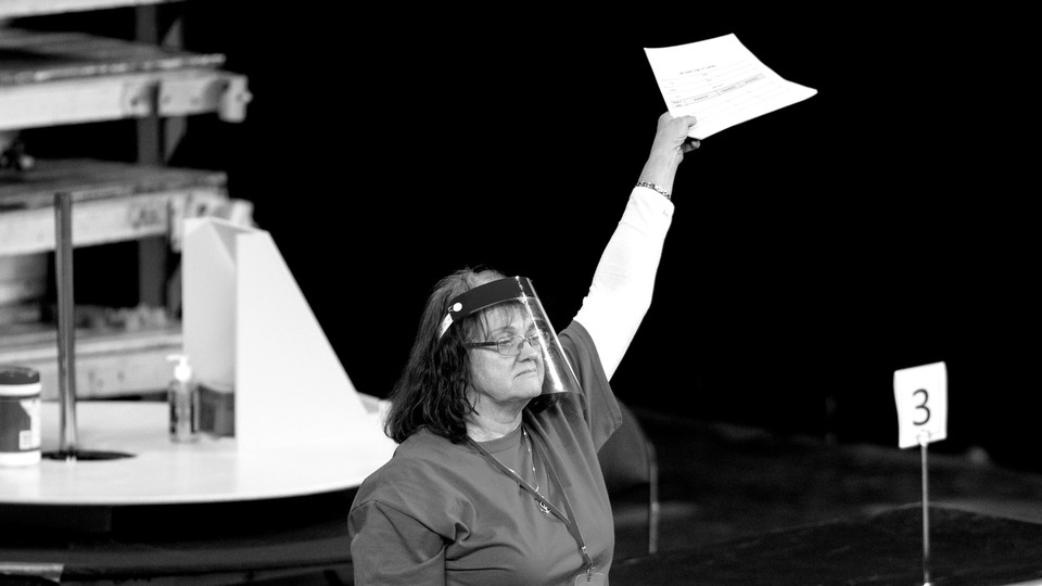 A woman wearing a clear face shield holds up a piece of paper. She is a contractor working to count ballots during the Arizona election recount.