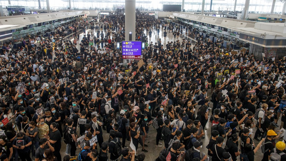 Protesters wearing black T-shirts crowd the departures hall of Hong Kong's international airport.