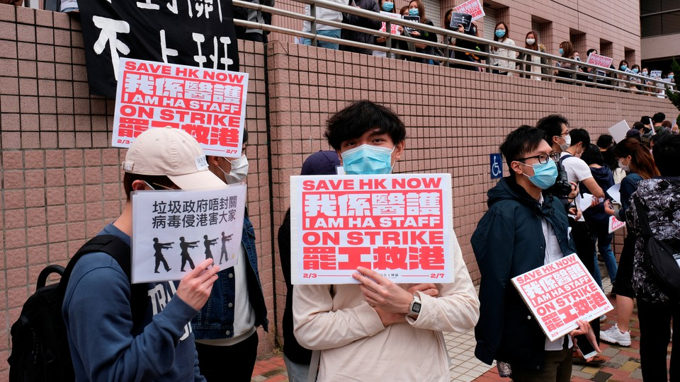 """Medical workers in Hong Kong protest with red and white signs that say """"Save HK now."""""""