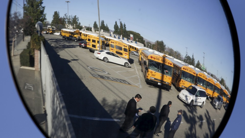 A parking lot filled with school buses is reflected in a bus mirror