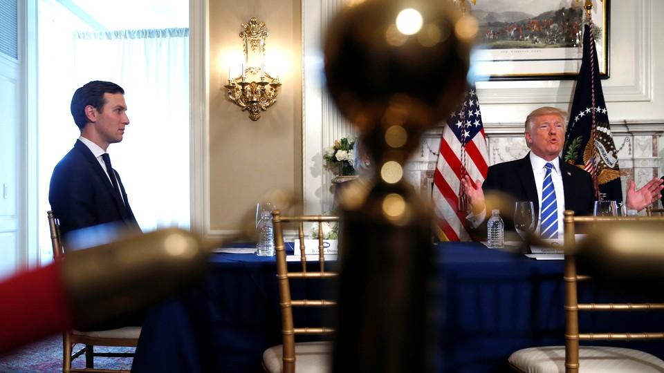 Jared Kushner sits at a table with Donald Trump.