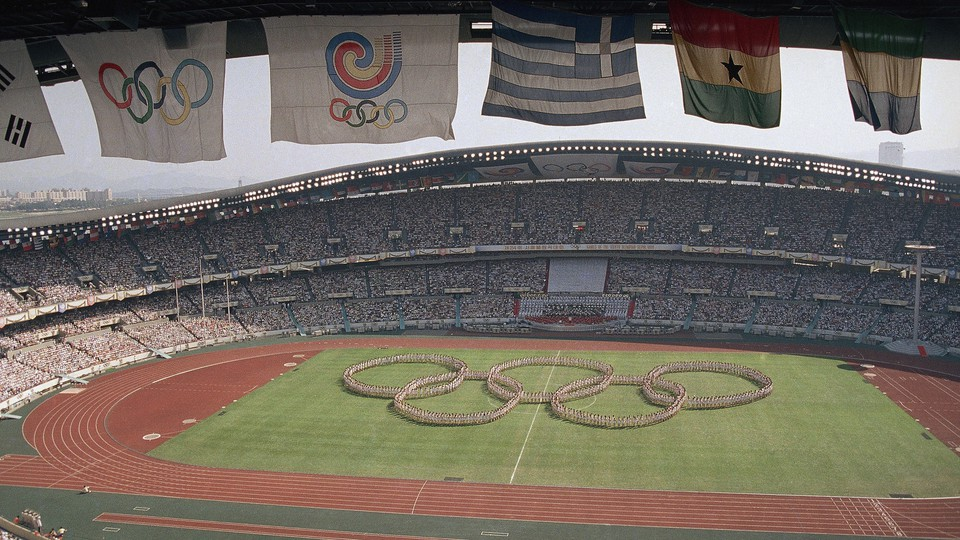 Flags frame the Olympic Stadium as participants form the Olympic rings on the field.