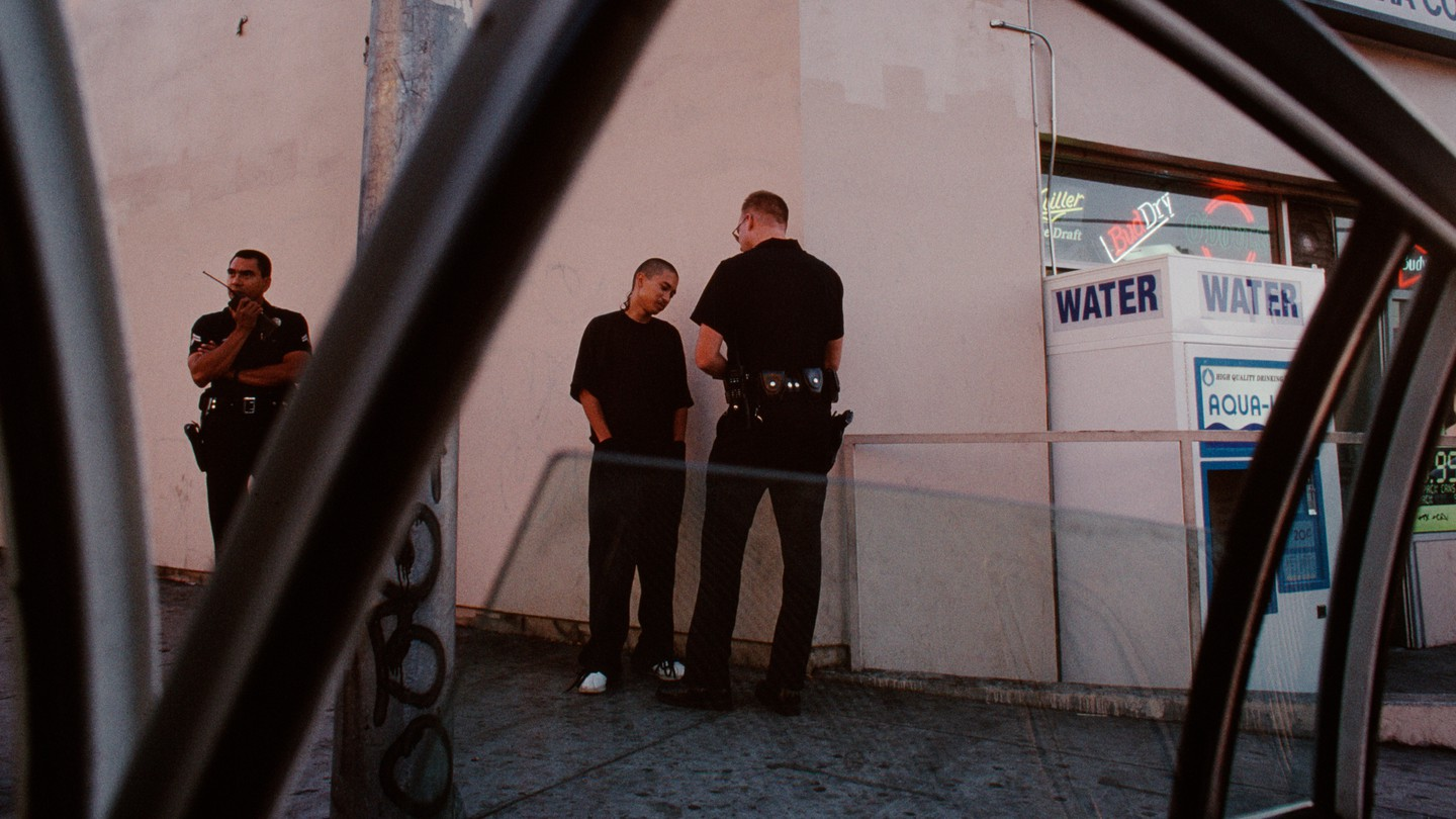 A young man receives a ticket for jaywalking in Pico Union.