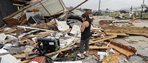 A woman stands among planks of wood, walls, and other debris wrecked by Hurricane Harvey