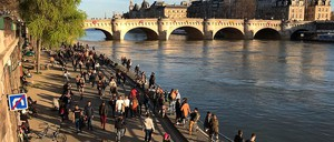 photo: Parisians walk along the Seine on Sunday, one day after Paris closed cafes and restaurants.