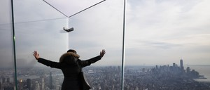 A woman looks out over Manhattan from a glass-walled observation deck in a skyscraper.