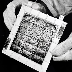 gloved hands hold a thermoelectric panel in a black and white photo