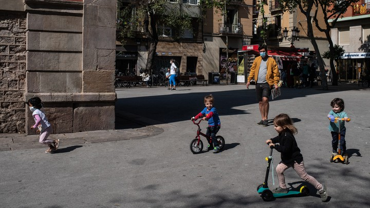 A man in a mask oversees a group of children playing on bikes and scooters in a plaza outside.