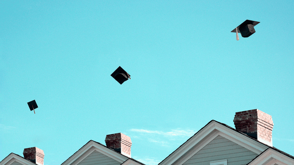 An illustration of graduation caps being thrown above houses.