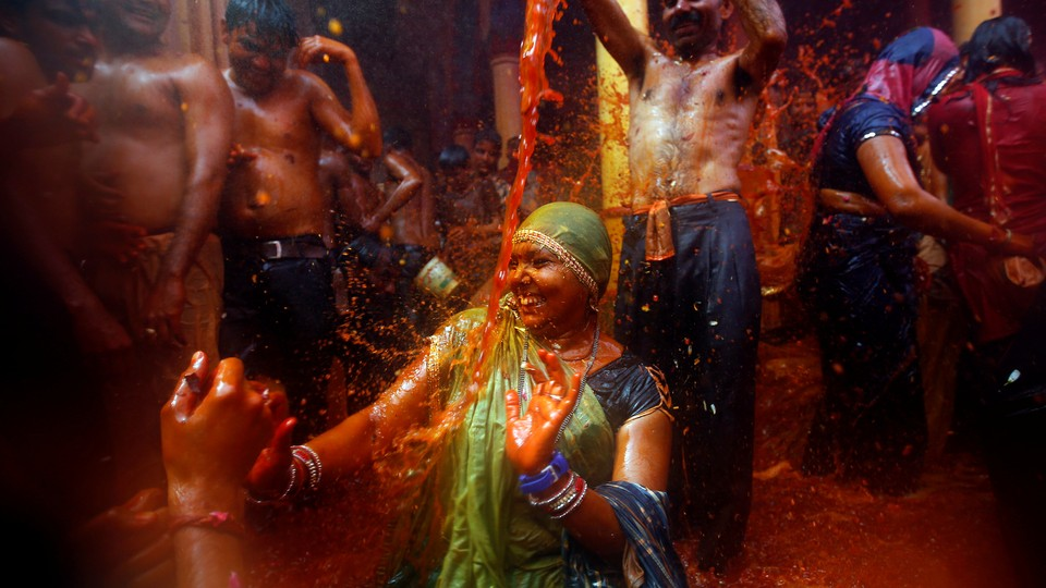 """A man throws water on a woman during """"Huranga,"""" a game played between men and women a day after Holi, near Mathura, India."""