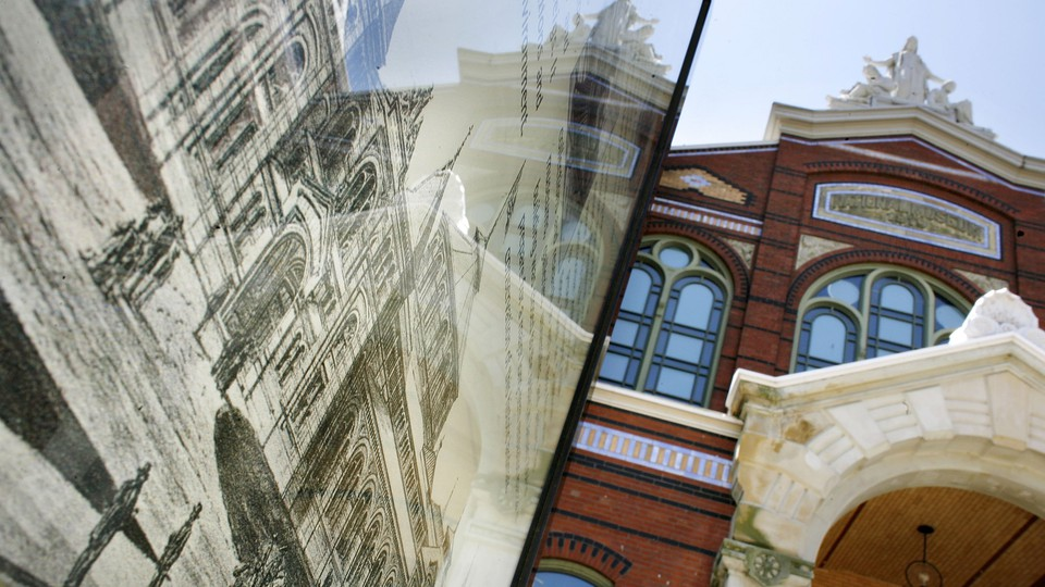 The Smithsonian Institution Arts and Industries Building is reflected in a sign displaying an antique drawing of the building