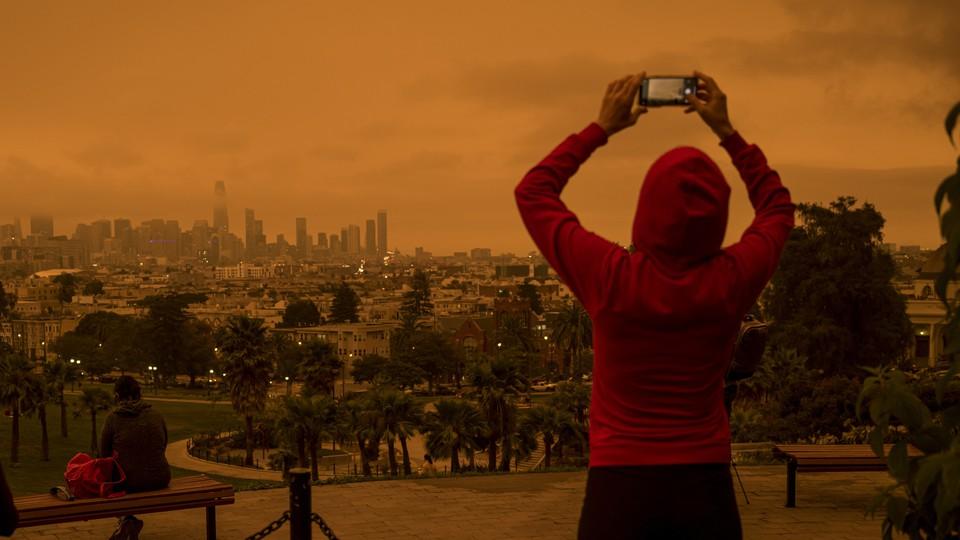 A woman taking a photo of an orange sky