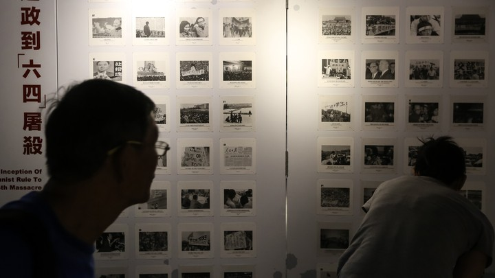 Visitors look at photographs at the June 4 Museum in Hong Kong during its reopening event in April.