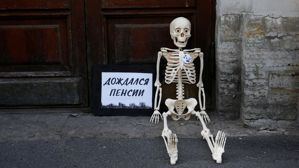 """During Russian protests against the raised retirement age, a fake skeleton is seated next to a sign that says, """"Waited for the pension."""""""