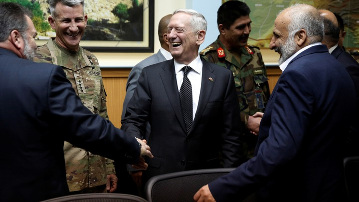 James Mattis stands in the center laughing and shaking hands with men in suits and military uniforms.