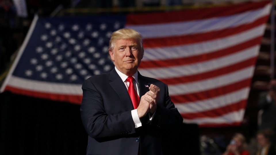 President Donald Trump stands in front of an American flag with clasped hands.