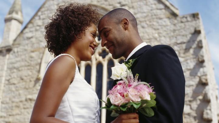A bride and groom embrace outside a chapel.