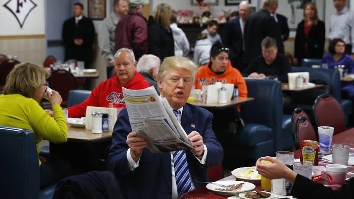 Republican candidate Donald Trump looks at a newspaper