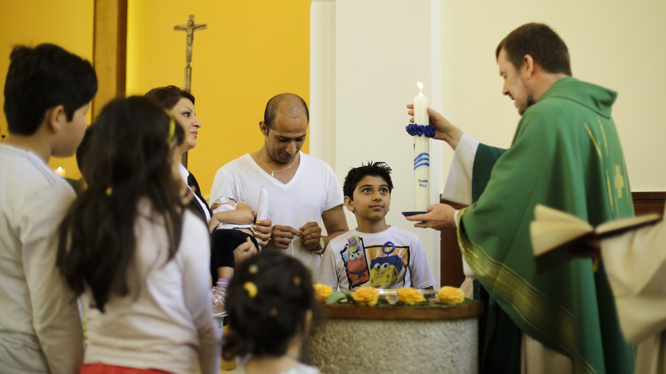 Pastor Gottfried Martens lights a candle during a service to baptize people from Iran, in the Trinity Church in Berlin, Aug. 30, 2015.