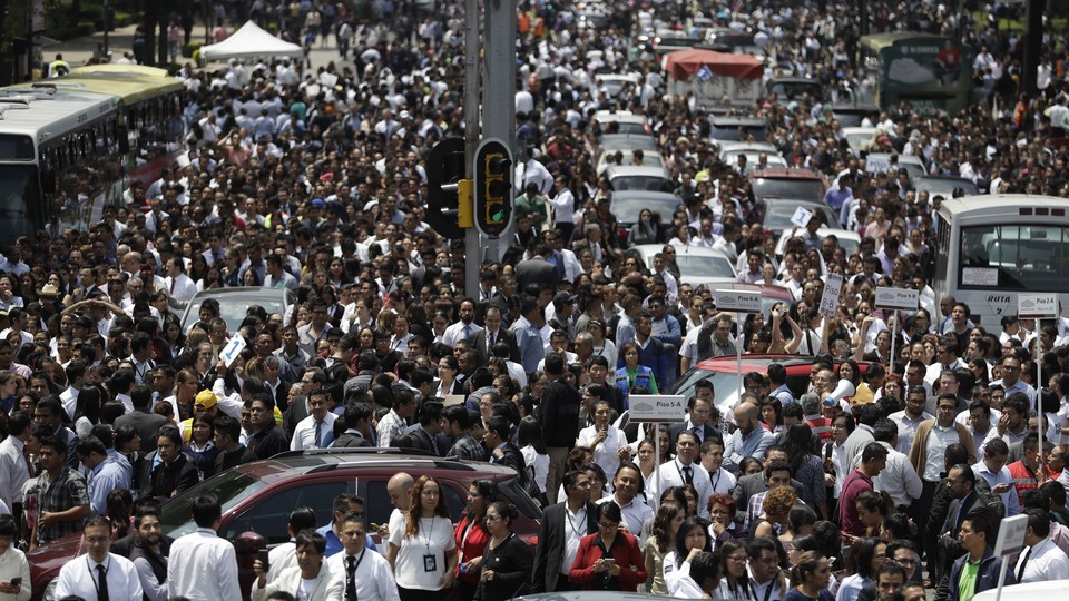 People evacuated from office buildings gather in Reforma Avenue