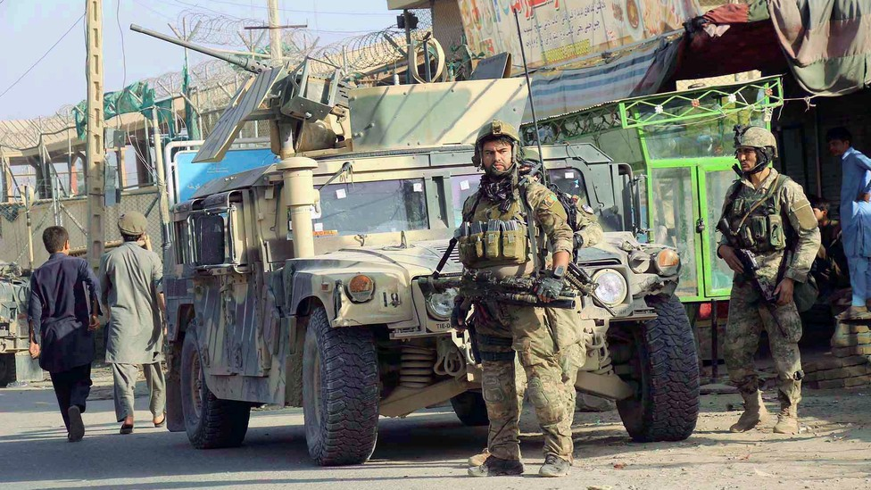 Afghan security forces keep watch in front of their armoured vehicle in Kunduz, Afghanistan, on Tuesday.