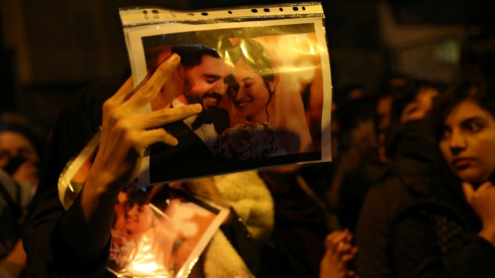 a woman holds a wedding picture depicting two victims of the crash of Ukraine International Airlines Flight 752.