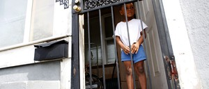 A young girl stands behind a grated door