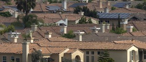 A neighborhood of Spanish-style houses in San Diego, several with solar panels on their roofs.