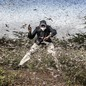 A man tries to scare away a large swarm of locusts.