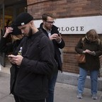 A photo of several people in a city starting at their smartphones.