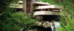 A modern stone and concrete house cantilevered over a waterfall.