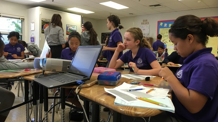 Students dressed in purple polos sit in a classroom with papers, pencils, and a laptop strewn in front of them.