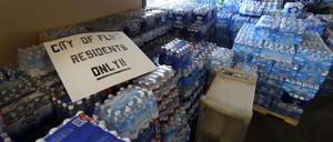 Hundreds of cases of bottled water sit inside a church.