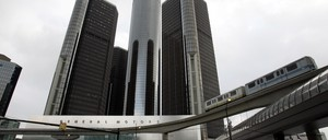 A photo of Detroit's elevated People Mover cruising past the Renaissance Center.