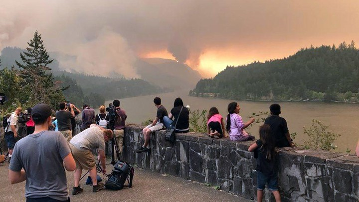 People watch a wildfire burning in a mountain range.