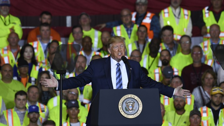 Trump gives a speech in front of workers wearing yellow vests.