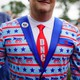 A smiling man is seen wearing a blazer featuring donkeys and a DNC tie