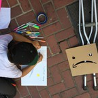 a photo of a child drawing an anti-Amazon protest sign at the Climate Strike march in San Francisco.