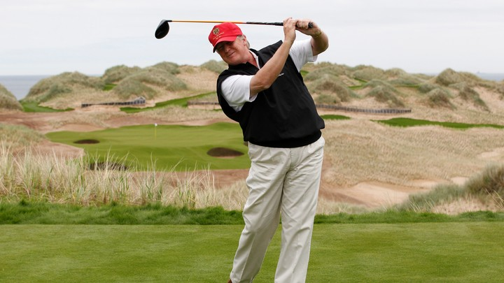 Donald Trump swings a club on a golf course in Scotland.