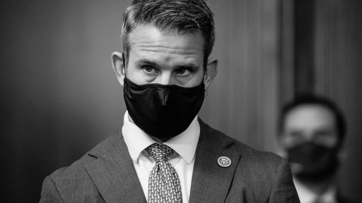 Representative Adam Kinzinger wears a black mask and suit