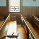 An empty pew with a Bible in a church