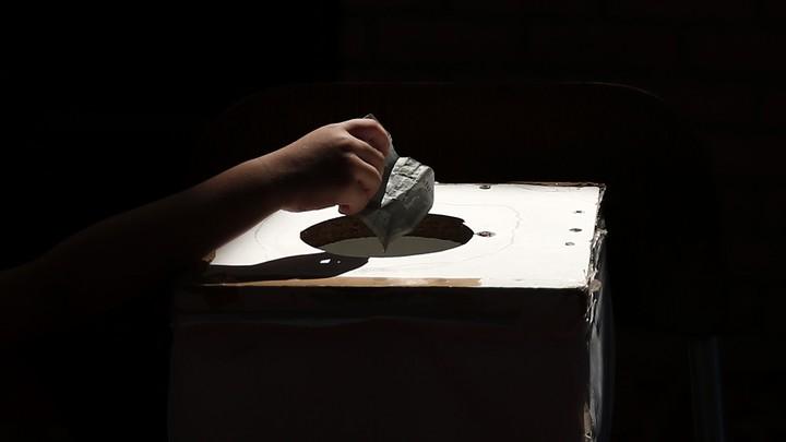 A hand drops money into a box.
