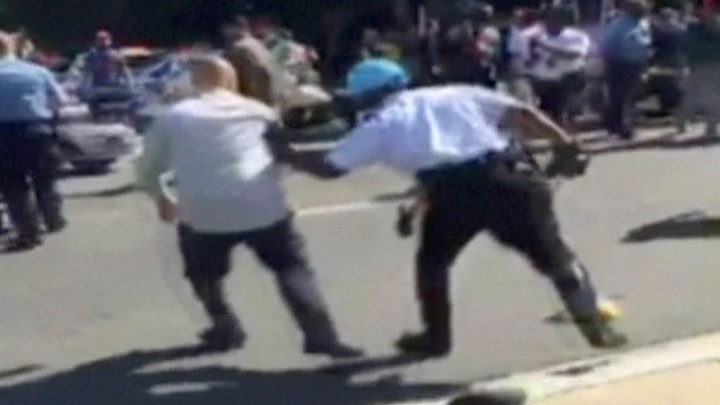 A still image of apolice officer chasing a protester during a violent clash outside the Turkish ambassador's residence between in Washington, D.C., on May 16, 2017.