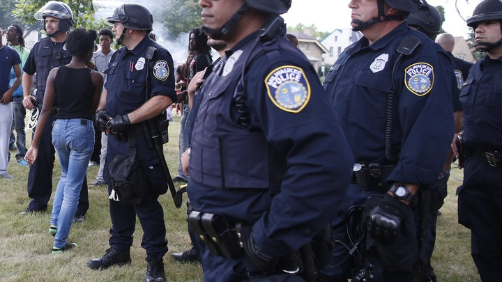 Five male police officers in full uniform and helmets stand looking toward the left; a young black woman walks through two of them with her back turned to the camera.
