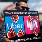 A man holds a sign reading: We are fighting for our rights, Uber and Lyft""