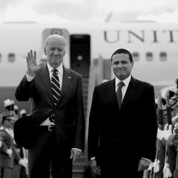 Joe Biden and Jill Biden wave to the camera and stand next to Guatemalan Foreign Minister Carlos Morales after descending in front of Air Force Two.