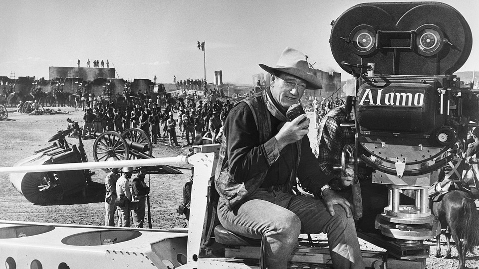 """John Wayne dressed as a cowboy directs the filming of """"The Alamo"""" in 1960."""