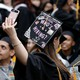 "A graduating student's cap reads ""Who's hiring?"""
