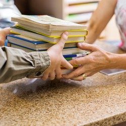 Someone hands another person a stack of books over a library counter. We can only see their arms and hands.