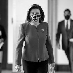 A black and white photograph of Nancy Pelosi walking toward the camera. She is wearing a pant suit and floral mask.